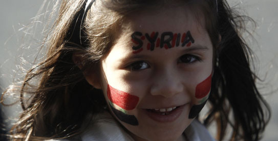 A Syrian girl living in Greece, with her face painted with the colors of the Syrian flag, attends a protest in Athens