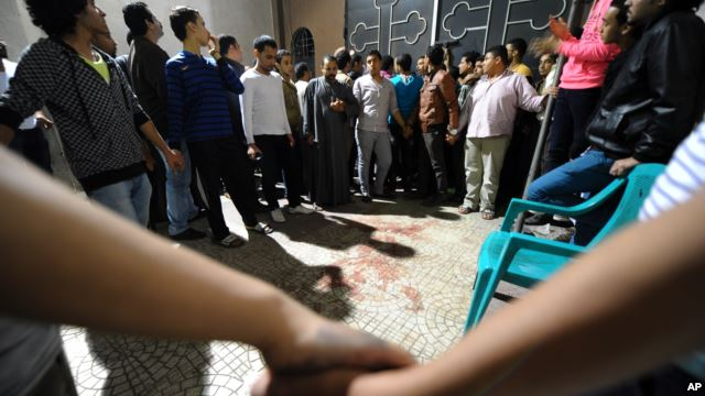 Egyptians gather at a Coptic Christian church in the Waraa neighborhood of Cairo late Sunday, October 20, 2013, after gunmen on a motorcycle opened fire on wedding guests gathered outside. (AP photo)