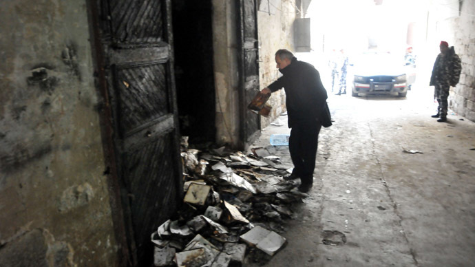 """A Lebanese soldier stands guard, on January 4, 2014 in north Lebanon's city of Tripoli, outside a decades-old library owned by a Greek Orthodox priest that was torched after """"a pamphlet was discovered inside one of the books that was insulting to Islam and the prophet Mohammad"""" said a source, who spoke to AFP on condition of anonymity. (AFP Photo)"""