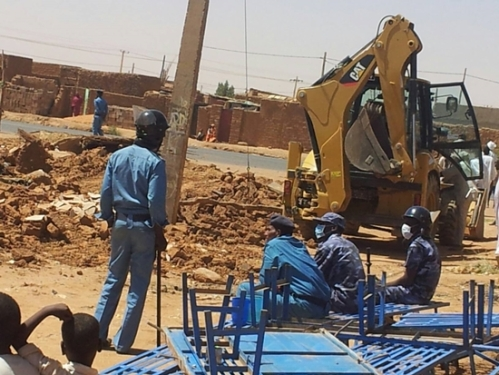 Police watch as Sudanese Church of Christ building in Omdurman is demolished. (Morning Star News)
