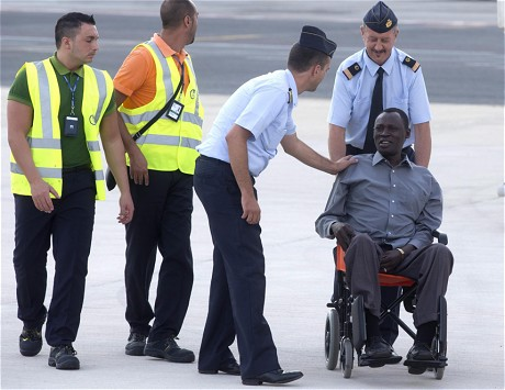 aniel Wani, husband of Meriam, is helped into the airport after arriving in Italy (EPA)