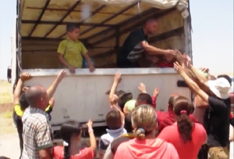 Christian refugees, who fled or were expelled from Mosul, crowd around a truck distributing food aid.