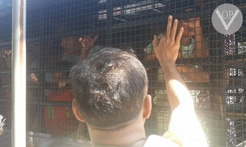 Child being comforted through cage of police van
