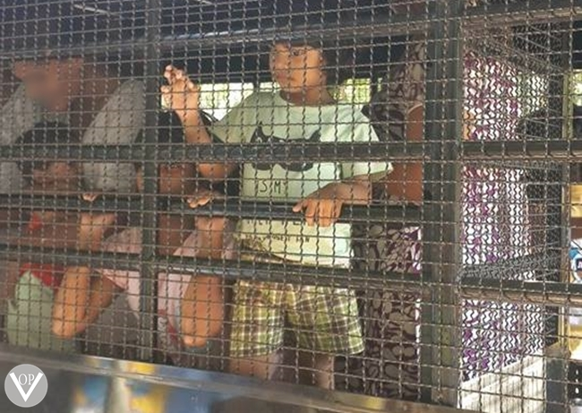 Child arrested with his mother and brought to court in caged police van. Children remain incarcerated along side their parents.