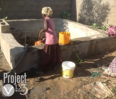 IDP child fetches water from local unsanitary well