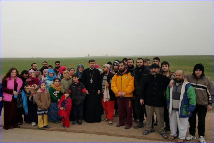 Bishop Aprim stands with the Assyrians released by ISIS.